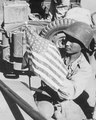 Soldier from China with an American flag in Burma on 6 February 1945, from- A U.S. Army soldier and a Chinese soldier place the flag of their ally on the front of their jeep just before the first... - NARA - 535573 (cropped) (cropped).tif