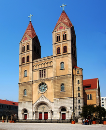 A cathedral in neo-Romanesque style, with twin spires topped with crosses, stands against the blue sky.