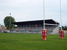 Vue d'un petit stade de rugby. Des poteaux de rugby et la pelouse au premier plan; une tribune couverte en béton et un projecteur sur sa droite en arrière-plan