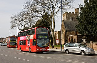 Edgware - Station Road. Here, all buses climb up the hill towards the station and the shops. St Margaret of Antioch Church can be seen in the background.