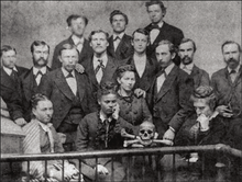 A black and white photograph of white male medical students posing with a human skull, with an African American woman (Sarah Loguen Fraser) sitting in the center front.
