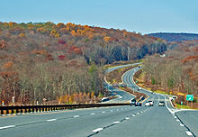 A divided highway in the middle of a late autumn wooded landscape curving up and down through a small valley with hills in the distance