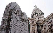 Imagem de um grande monumento de pedra exibindo os dez mandamentos com o Estado Capitol Texas em Austin em segundo plano.  A imagem era parte de um comunicado de imprensa quarta-feira, Março segunda, de 2005, pelo então Procurador Geral Abbott.