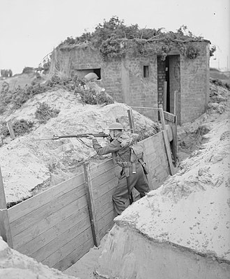 18th Infantry Division (United Kingdom) - A lone soldier of the 4th Battalion, Royal Norfolk Regiment, mans a trench near a pillbox at Great Yarmouth, Norfolk, 31 July 1940.