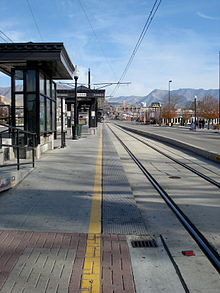 An empty island platform station located next to the tracks in the median of the street with canopies visible. Businesses line the street with mountains visible in the distance.