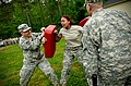 U.S. Army Pvt. Deidra Reinatdixon, center, with Headquarters and Headquarters Company, 105th Military Police Battalion, North Carolina Army National Guard, makes her way through a defense course during oleoresin 130501-Z-AY498-016.jpg