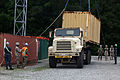 U.S. Naval personnel from Navy Cargo Handling Battalion, and Marines from Combat Logistics Battalion 8, Transportation Support Company, work together to load an ISO container onto a 7-ton during 120613-M-KS710-045.jpg