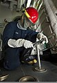 U.S. Navy Boatswain's Mate Seaman Apprentice Alexander Evans removes deck valve covers aboard the guided missile destroyer USS Mason (DDG 87) during a damage control exerciseJan. 3, 2014, while underway in 140103-N-PW661-018.jpg