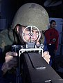 US Navy 030201-N-1356A-011 Personnelman 3rd Class peers through the sight of a .50 cal gun mount to locate an incoming target.jpg