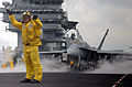 US Navy 040414-N-4308O-017 Aviation Boatswain's Mate 2nd Class Franklin Santiago signals an aircraft across the flight deck as an F-A-18C Hornet prepares to launch from the flight deck of USS Harry S. Truman (CVN 75).jpg