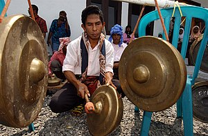 Abui people - A man playing the gong for a ceremonial song and dance as an appreciation to the United States Navy for providing humanitarian assistance and medical aid to the locals affected by the November 2004 earthquake that struck Alor Island.