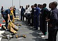 US Navy 090213-N-1655H-002 Africa Partnership Station embarked trainees observe crew members aboard the amphibious transport dock ship USS Nashville (LPD 13) demonstrate the proper donning of a firefighting ensemble during dama.jpg