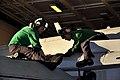 US Navy 091225-N-8421M-128 Aviation Electrician's Mate 2nd Class Andrew Savini and Aviation Electrician's Mate Airman Dexter Fredinburg conduct maintenance on an F-A-18C Hornet.jpg