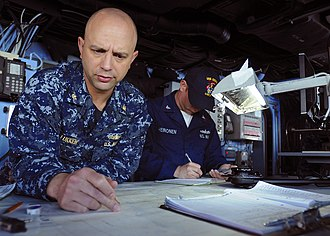 United States Fleet Activities Sasebo - Cmdr. Mark Lukken plots a course on the chart table aboard the forward-deployed amphibious assault ship USS Essex (LHD-2), SASEBO, Japan (June 8, 2010)