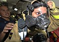 US Navy 101122-N-6499D-081 Damage Controlman 2nd Class Dean Bonoan helps Operations Specialist Seaman Kai Varela don a firefighting suit during dam.jpg