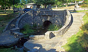 A decorative stone bridge, with curving stairs down to the water below on either side, in a park