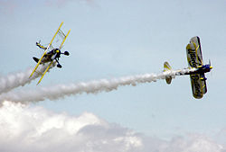 The UK Utterly Butterly display team perform an aerobatic manoeuver with their Boeing Stearmans, at an air display in England.