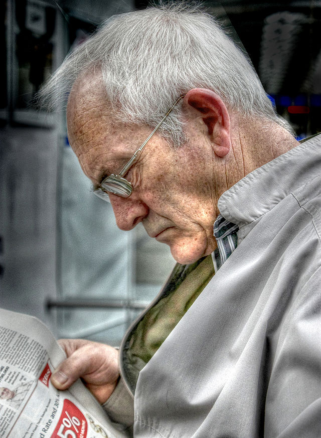 Part of the aging population, an elderly man reads a newspaper.