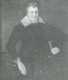 Formal portrait of Sir William Davenport, standing. He has a long pale face, hair combed back from his forehead and a trim full-face beard. He wears dark clothing with a falling collar and cuffs bordered with needle lace and a ring on his finger