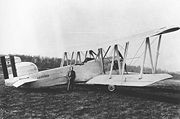 A monochrome photograph of a biplane parked on an airfield, with a man posed leaning against its fuselage with his hands in his pockets