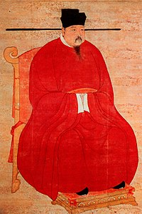 A portrait oriented scroll depicting a man in thick red robes, black pointed shoes, and a bucket shaped black hat with long, thin protrusions coming out horizontally from the bottom of the hat, sitting on a throne.