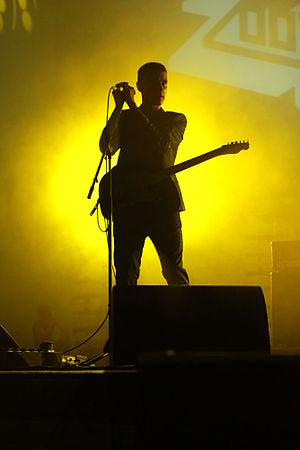 Johnny Blake stands on a stage holding a microphone in both hands. He wears a guitar, there are speakers in front of him and behind him, and a bright green light shines behind him