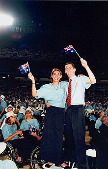 Two people standing on folding chairs and holding small Australian flags