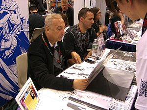 Sandu Florea - Florea looking over an aspiring artist's portfolio at the 2011 New York Comic Con.