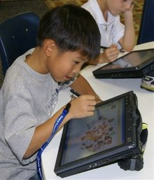 A young Asian boy in a gray T-shirt at a round table using a tablet computer