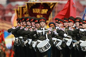 "Corps of drums - Corps of drums of the Moscow Military Conservatoire at the Victory Parade on Red Square, 2010. Note the red and white ""swallows' nests"" on the shoulders, characteristic of musicians' uniforms in European armies."