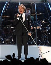 A man on a stage, wearing a suit and holding a mic and its stand at an angle. Behind him, a man is playing a drum set.