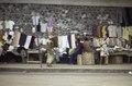 ASC Leiden - F. van der Kraaij Collection - 05 - 036 - Street vendors for textile and clothes on a sidewalk alongside a wall - Monrovia, Waterside, Montserrado, Liberia, 1975.tif