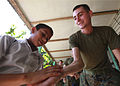A student high-fives U.S. Marine Corps Cpl. David J. Shields, s logistics-embarkation and combat support specialist assigned to Marine Air Communications Squadron 2 and attached to Special Purpose Marine 100825-M-PC721-023.jpg