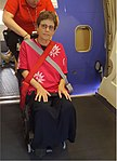 A wheelchair bound customer on an aisle-chair, tied with three straps, to be carried into an airplane seat.jpg
