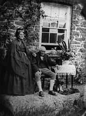 A woman and a man outside a house