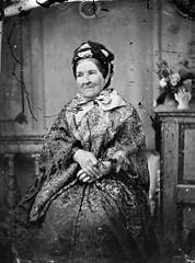 A woman sitting and wearing a shawl
