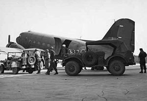 A large propeller driven aircraft on a runway. There are three jeeps nearby, and some men wearing steel helmets.