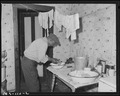 Amos Wilson, miner, washing hands in kitchen of his home. Koppers Coal Division, Federal ^1 Mine, Grant Town, Marion... - NARA - 540277.tif