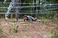 An Army Junior Officer Training Corps cadet low-crawls underneath a barbed wire obstacle on the 7th Special Forces (Airborne) compound.jpg