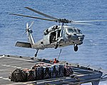 An MH-60S Sea Hawk helicopter picks up cargo from the flight deck of USNS Leroy Grumman. (29206264772).jpg