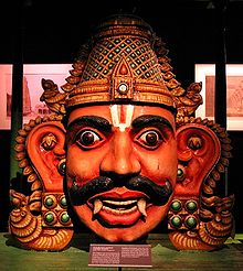 A crowned male wooden head with big eyes and ears, a Vaishnava tilak and bushy brows and large moustache. He has reddish skin, and two large canine teeth that hang down lower than his bottom lip. His eyes are wide open and he has large S-shaped ears that reach down to his chin. In the dark background, images are displayed on the back wall under lighting.