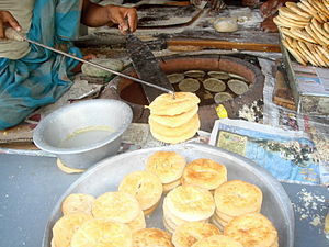 Bakarkhani - Bakarkhani being made in a Dhaka. They can be seen lining the walls of the Tandoor oven.