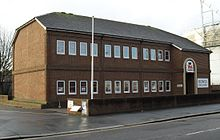 "Three-quarter view of a two-storey brown brick building with a shallow, grey, partly hipped roof.  The two storeys are separated by a thin band of projecting bricks.  Each floor has three sets of four rectangular windows.  To the right, a projecting section includes a round-headed entrance door, the words ""BOWLS ENGLAND"" on a white background, and a red and blue logo consisting of a heraldic lion and a crown."