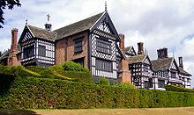 The exterior of a large house. There are several chimneys, leaded windows and wings. In the foreground are two rows of hedges.