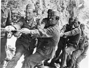 a number of men in SS uniforms and wearing fez headgear straining to pull on a rope