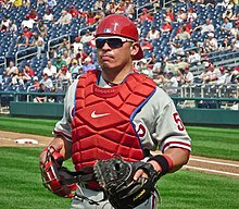 An olive-skinned man wearing a gray baseball jersey, red chest protector, red backwards baseball helmet, and sunglasses carrying a catcher's mask in his right hand and wearing a catcher's mitt on the left
