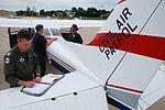 Civil Air Patrol pilot Tom Pflug checks his flight log as CAP photographer Erich Deitenbeck discusses the days photo opportunities with FEMA's Natasha Wilkins.jpg
