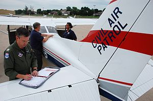 Nebraska Wing Civil Air Patrol - Civil Air Patrol pilot Tom Pflug checks his flight log as CAP photographer Erich Deitenbeck discusses the days photo opportunities with FEMA's Natasha Wilkins.