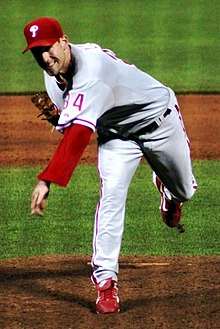 "A man in a gray baseball uniform with red trim and the number ""34"" on the sleeve in red and a red baseball cap throwing a baseball (unseen) from a dirt mound"