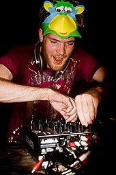 A white man with red hair and a slight beard manipulating the controls of a piece of music mixing equipment. He has headphones around his neck and a mask resembling a multi-coloured monkey pushed up onto the top of his head.